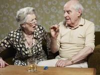 Senior woman looks shocked as senior man smokes cigar