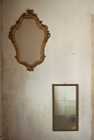 Two old mirrors hanging on bare wall