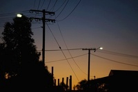 Silhouetted utility poles and roof of a building at dusk
