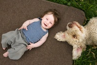 A baby girl and dog lying outside