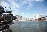 A television camera filming the Brooklyn Bridge and Manhatta