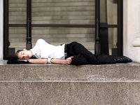 A young sleeping businessman lying on steps outside a buildi