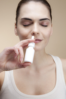 A serenely smiling young woman inhaling nasal spray