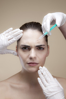 A worried looking young woman receiving Botox injections