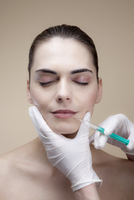 A serene young woman receiving collagen injections into her