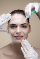 A smiling young woman receiving Botox injections