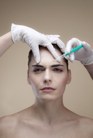 A serious young woman receiving Botox injections