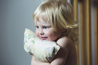 Blonde haired girl hugging pillow