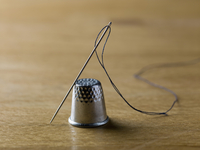 A threaded needle balanced against a shiny metal thimble