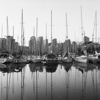 Skyscrapers and boats both reflected in water of marina in V