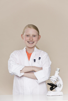 A smiling girl wearing a lab coat standing next to a microsc