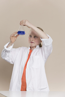 A girl wearing a lab coat and holding a conical flask with b