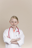 A smiling girl wearing a lab coat with a stethoscope around