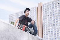 Thoughtful young man with skateboard sitting against building