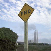 A dead end road sign in foreground, smoke stacks emitting smoke in background