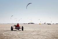 Boy riding kite buggy on beach