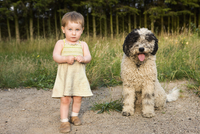 Baby girl standing with Portuguese Water Dog, portrait