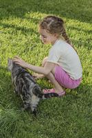 Full length side view of girl stroking cat in park