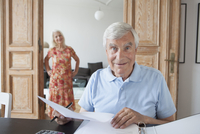 Portrait of surprised senior man checking financial documents at home with woman in background