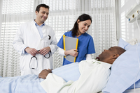 A doctor and nurse talking to a patient lying in a hospital bed