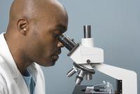 Technician looking into microscope