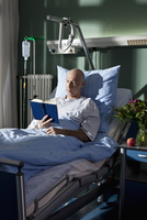 A man reading a book in a hospital bed