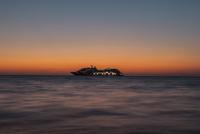 Silhouette cruise ship sailing on sea at sunset