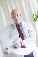 Mature doctor examining euro symbol with stethoscope at clinic