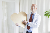 Doctor with eyes closed examining heart shape with stethoscope at clinic