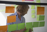 Man putting adhesive notes on glass wall in office