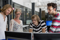 Office colleagues looking at computer in office