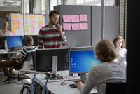 Colleagues working in office, man talking on landline phone