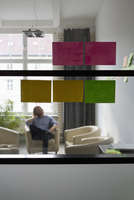 Adhesive notes on glass wall, man sitting on sofa in background