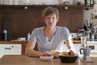 Young man sitting at dining table with breakfast, portrait