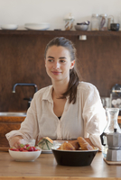 Young woman sitting at dining table with breakfast, smiling