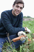 Man harvesting carrot in field, portrait