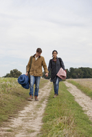 Young couple carrying camping accessories walking through dirt track