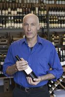 Mature man holding wine bottle in wine shop, portrait