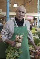 Mature man holding turnip, portrait
