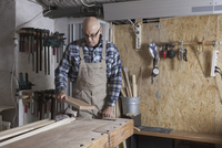 Mature man working in carpenter shop