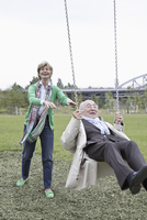 Couple playing on park swing