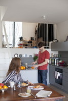 Woman sitting at dining table while man preparing breakfast in kitchen