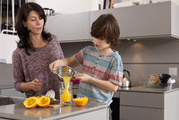 Mother and son making orange juice
