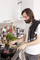 Man preparing meat in domestic kitchen