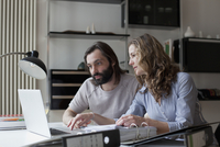 Mid adult couple working on laptop at home
