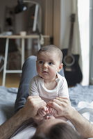 Cute baby girl sitting on father at home
