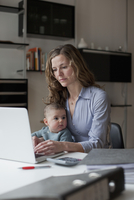 Woman using laptop while sitting with baby girl at home