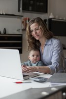 Woman working on laptop while sitting with baby girl at home