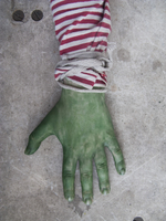 Close-up of green painted hand against gray background