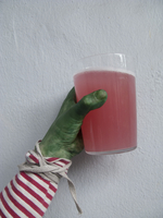Close-up of green painted hand holding glass full of red drink against white wall